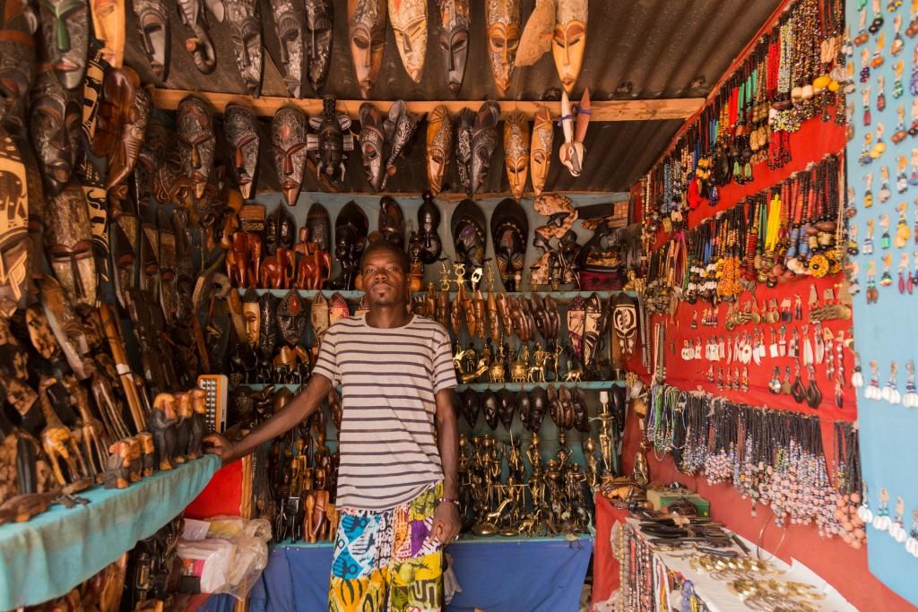 Tim, artiste Burkinabé, devant son stand le long du canal
